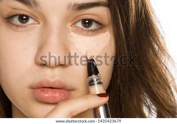 Young beautiful woman applying concealer on white background
