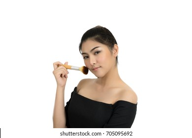 Young beautiful woman applying cosmetic powder brush on face isolated over white background.