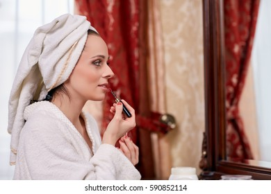 Young beautiful woman applying  gloss for lips sits before a house  dressing table.
