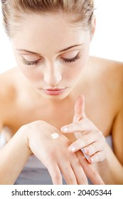 Young beautiful woman applying hands cream and looking at camera