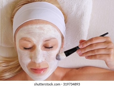 Young beautiful woman applying homemade facial mask i at home.Skin care, beauty treatments.