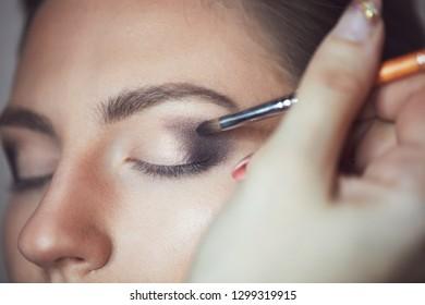 Young beautiful woman applying make-up by make-up artist. Process of making makeup.