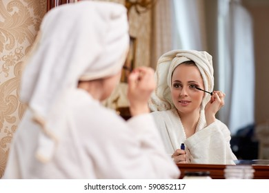 Young beautiful woman applying mascara for eyelashes sits before a house  dressing table.