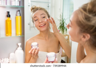 Young beautiful woman applying moisturising cream on skin in bathroom. Standing in towel with little jar of moisturizer, looking in the mirror, laughing and having fun.  Morning skincare routine.
