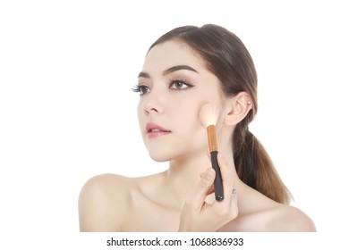 young beautiful woman applying powder on cheek with brush