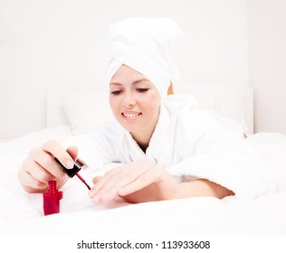 young beautiful woman applying red nail polish in bed at home