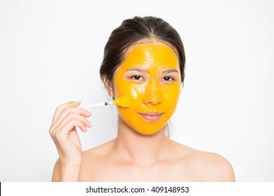 Young beautiful woman applying yogurt and turmeric facial mask Skin care, beauty treatments on white background