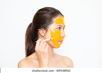 Young beautiful woman applying yogurt and turmeric facial mask Skin care, beauty treatments on white background