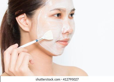Young beautiful woman applying yogurt facial mask Skin care, beauty treatments on white background