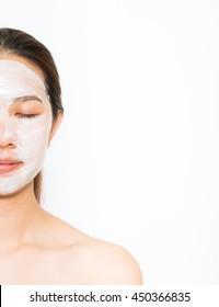 Junge schöne Frau, die Jogurt Gesichtsmaske Haut pflegt, Schönheitsbehandlungen auf weißem Hintergrund