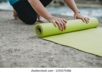 Young beautiful woman arranges the mat on the ground to do yoga exercises in summer on the bank river