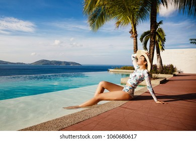The young, beautiful woman of Asian appearance, in bikini, has a rest in the pool overlooking the sea