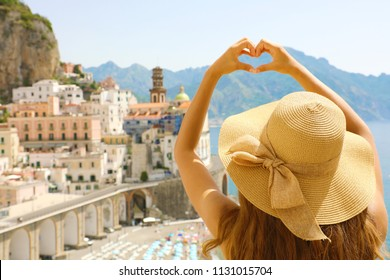 Young beautiful woman in Atrani, Amalfi Coast, making hands shaped heart on spring summer warm sunny day. Girl with hat happy outdoors in her travel in Southern Italy.