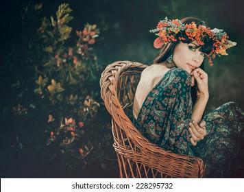 Young beautiful woman in autumn wreath on head