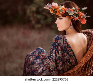 Young beautiful woman in autumn wreath on head