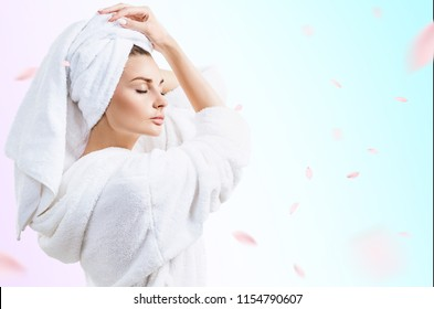 Young beautiful woman in bathrobe over fresh blue background with swirl petals.