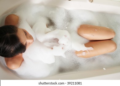 Young beautiful woman in the bathroom taking a bath