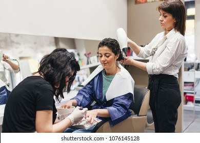 Young beautiful woman in a beauty salon while the hairdresser arranges her hair and gets her a manicure