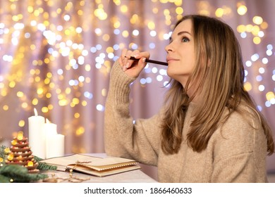Young beautiful woman beige knitted sweater writing shopping list,  Christmas letter or wish list for christmas in festive interior at home. Christmas atmosphere.Goals plans. Sail Champagne color.