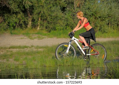 Young beautiful woman with bicycle going through water by the river