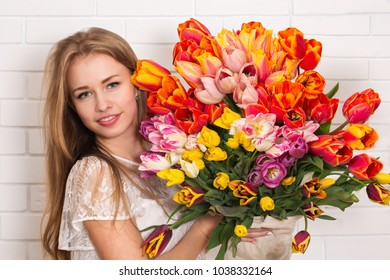 Young beautiful woman with a big bouquet of tulips