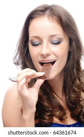 Young beautiful woman bites off slice from chocolate bar, on white background.