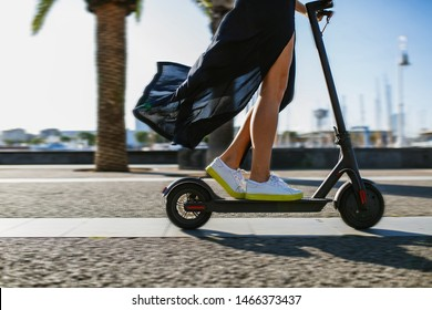Young beautiful woman in a black dress riding an electric scooter to work, female legs on electric scooter, electric transport, ecology, ecological transport, sunset, electric skateboard, 4k - Imagen