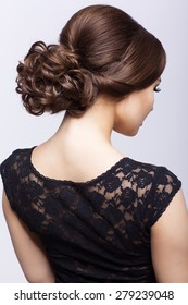Young beautiful woman in black dress from back side on gray background