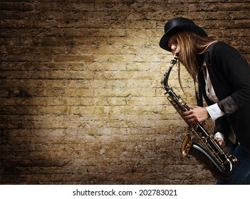 young beautiful woman in black hat with saxophone