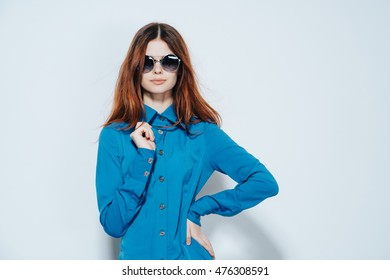 young beautiful woman in a black round glasses and a blue blouse strict
