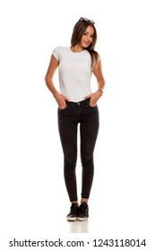 Young beautiful woman in black tight jeans posing on white background