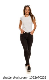 Young beautiful woman in black tight jeans walking on white background