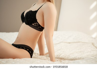 a young beautiful woman in black beautiful underwear meets a sunny morning in the bedroom on the bed. selective focus with a small focus area.
