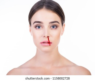 Young beautiful woman with bleeding nose. Anti-glamor. Beautiful woman blood on her face. Domestic violence, tyranny, despotism, women's rights, victim of house tyrant concept.