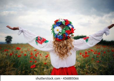 young beautiful woman with blond long hair in national dress red skirt and a white shirt with a wreath of flowers in a field of poppies and wheat