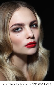 Young beautiful woman with blonde curly hair and red lipstick