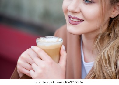 Young beautiful woman with blonde long curly haur sitting in a cafe and drinking coffee . Close up portrait .