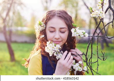 young beautiful woman in the blossoming spring garden