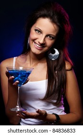 Young and beautiful woman with a blue cocktail in the nightclub