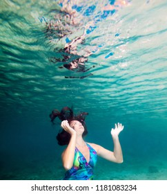 Young beautiful woman in blue dress underwater