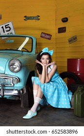 Young beautiful woman in blue dress with polka dots with bow on head smiling looking at camera and holding hands under head near blue car