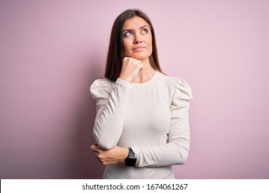 Young beautiful woman with blue eyes wearing casual white t-shirt over pink background with hand on chin thinking about question, pensive expression. Smiling and thoughtful face. Doubt concept.