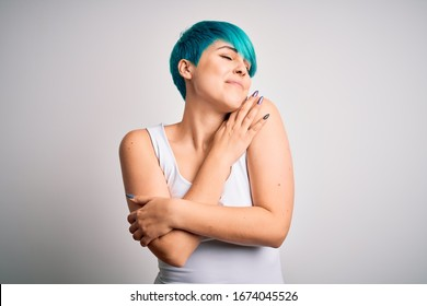Young beautiful woman with blue fashion hair wearing casual t-shirt over white background Hugging oneself happy and positive, smiling confident. Self love and self care