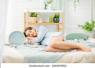 Young and beautiful woman in blue shirt sleeping with big alarm clock on the comfortable bed at home