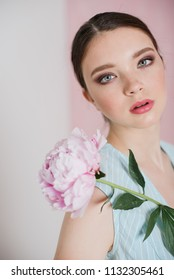 A young beautiful woman in a blue striped dress with gathered hair is standing holding a peony in her hands. Cropped photo.