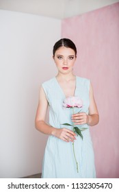 A young beautiful woman in a blue striped dress with gathered hair is standing holding a peony in her hands.