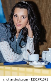 Young beautiful woman in blue sweater sits at table in restaurant and drinks tea.