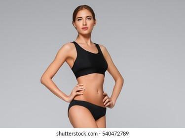 Young beautiful woman body on gray background in black sport clothes