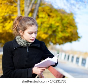 Young beautiful woman with book on bench in park