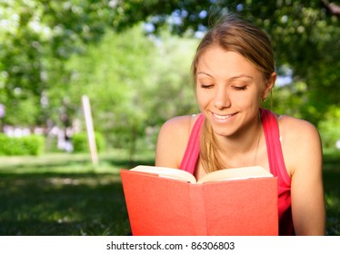 young beautiful woman with the book outdoors
